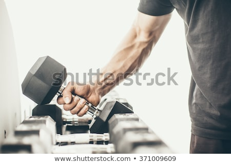 Athletic man with dumbbells on the black Stock photo © vlad_star