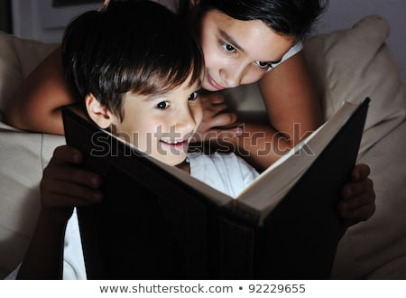 Stock photo: Boy and girl reading light book at night, children concept