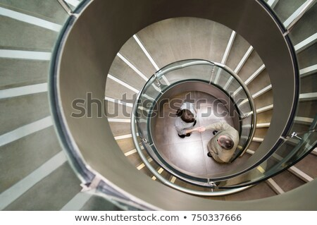 Business duo shake hands in a stairwell Stock photo © IS2