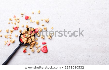 Organic cereal granola bar with berries with honey spoon and jar of oats on marble background. Top v Stock photo © DenisMArt