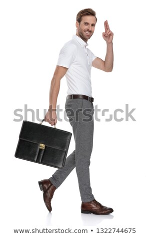 Stock photo: side view of a smiling  man holding briefcase and greets