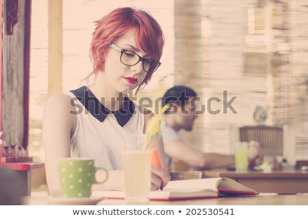 Serious red haired teenage girl studying at the table Stock photo © deandrobot