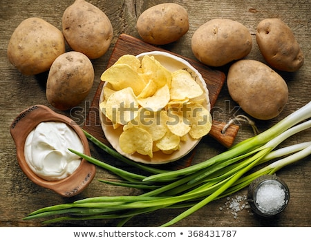 Fresh organic homemade potato crisps chips with sour cream and red onions on paper on dark wooden ba Stock photo © DenisMArt