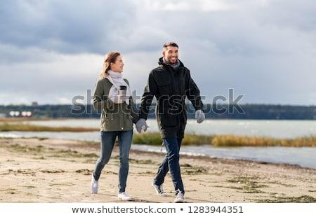 couple with tumbler walking along autumn beach Stock photo © dolgachov