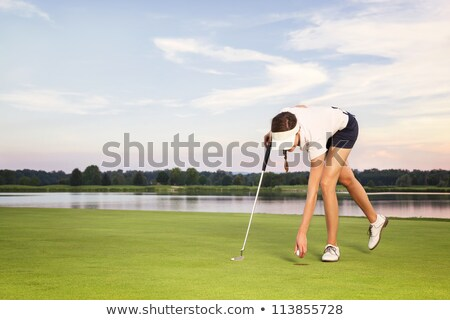 Girl golf player picking up ball from cup. Stock photo © lichtmeister