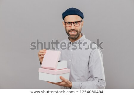 Handsome European man with thick stubble, pleasant smile, holds boxes in hands, opens gift with happ Stock photo © vkstudio