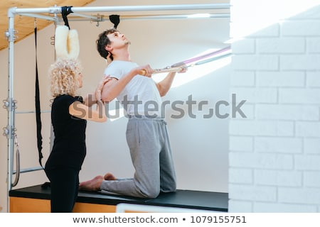 Pilates aerobic personal trainer man in cadillac Stock photo © lunamarina