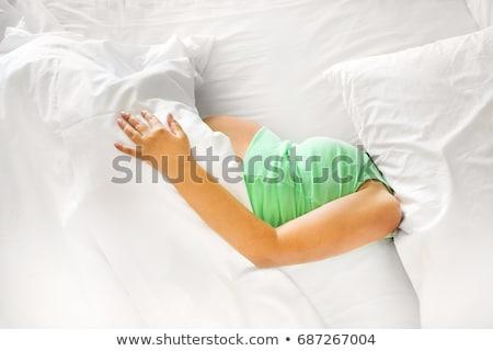 pregnat woman lying on bed stock photo © phbcz