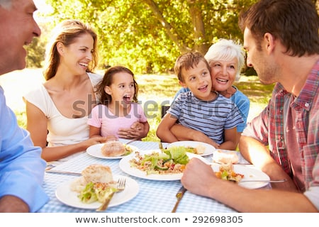 Family eating together outdoors Stock photo © HASLOO