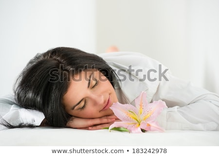 front view of young woman sleeping on massage table in health sp stock photo © hasloo