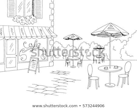 Table with chairs on stone paved old street and colored houses f Stock photo © pixachi