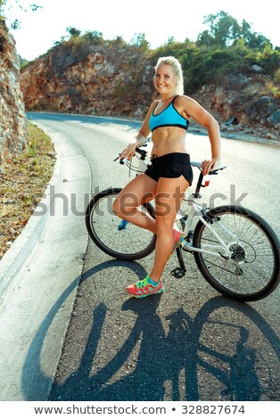 athletic woman standing near her bicycle on a mountain road stock photo © vlad_star
