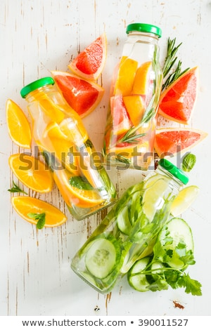 Stock photo: Infused water with citrus and mint in glass bottles on wooden ba