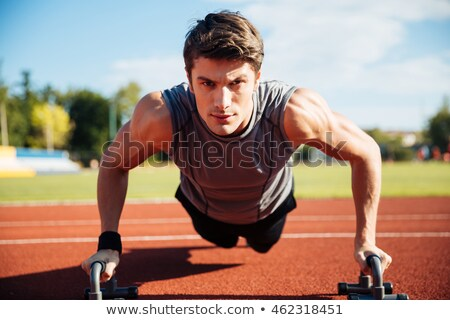 Young male athlete makes push ups on a racetrack Stock photo © deandrobot