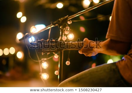 Young man sitting and playing acoustic guitar Stock photo © manaemedia
