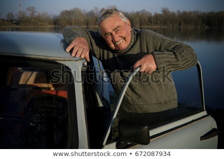 Senior man standing by car on riverside Stock photo © IS2