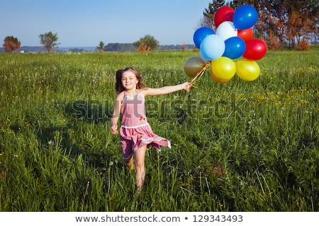 Happy little girl playing with large bunch of helium filled colorful balloons Stock photo © Len44ik