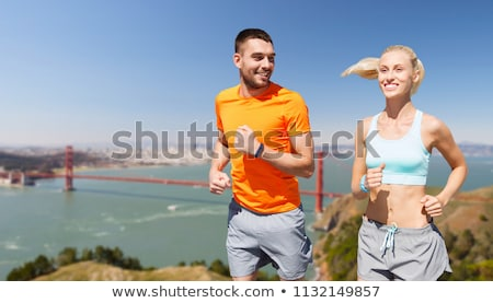 couple running over golden gate bridge background Stock photo © dolgachov