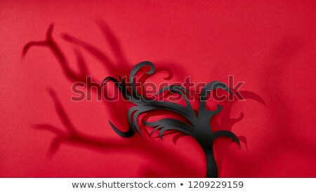 On a red background scary shadows and handcraft paper branches with copy space for text. Halloween c Stock photo © artjazz
