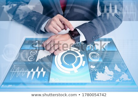 businessman with smart watch and earth hologram stock photo © dolgachov