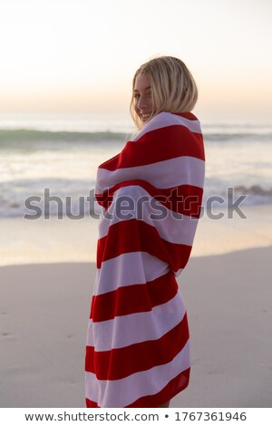 Woman standing on beach with flag wrapped around her Stock photo © lovleah