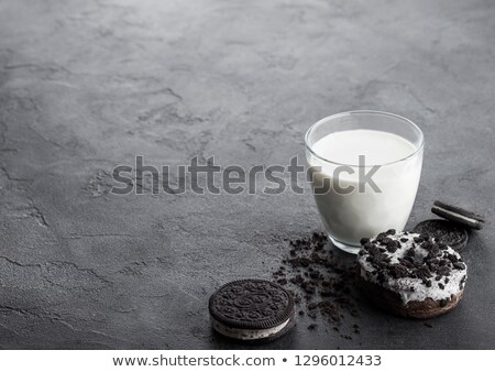 glass of milk and black sandwich cookies with doughnut and ice cream on black stone kitchen table ba stock photo © denismart