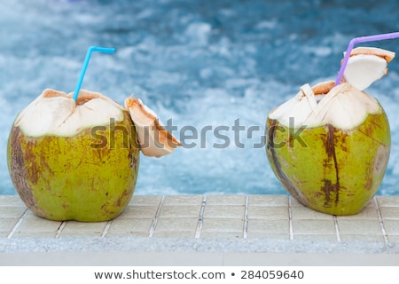 Green coconut with a straw on the edge of a pool  Stock photo © dashapetrenko