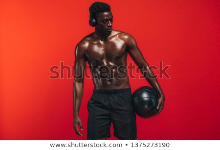 Young shirtless African muscular athlete with ball standing on basketball court Stock photo © pressmaster