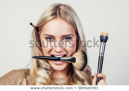 Make-up with black eyeliner close-up. Make-up artist applying eyeliner pencil on a model with green  Stock photo © serdechny
