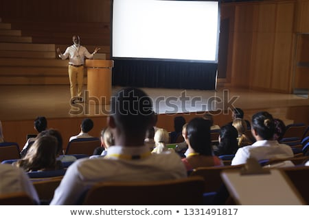 Front view of African-American usinessman standing at podium on stage in auditorium  while looking a Stock photo © wavebreak_media