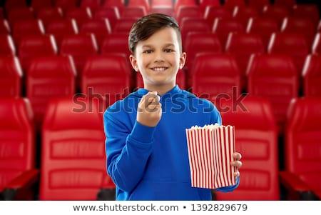 happy smiling boy in blue hoodie eating popcorn Stock photo © dolgachov