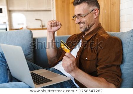 Portret zadowolony przystojny mężczyzna za pomocą laptopa okulary Zdjęcia stock © deandrobot
