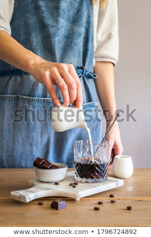 Barista hands pouring milk into a glass of coffee on a wooden brown table. Slow motion, Full HD vide Stock photo © artjazz