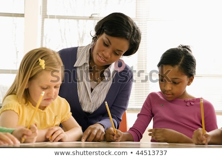 teacher helping students with schoolwork in school classroom ho stock photo © hasloo