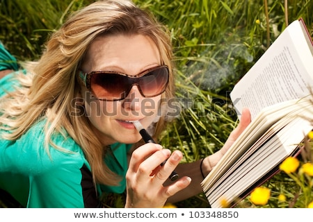 Blonde woman with book evaporated electric cigarette stock photo © Pasiphae