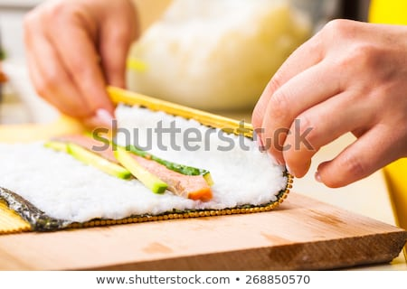 chef turns nori sheet with filling  Stock photo © OleksandrO
