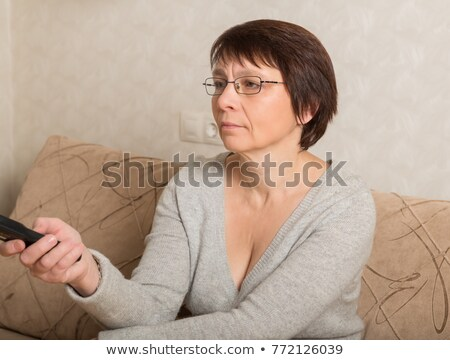 elderly woman on the sofa with television remote control stock photo © ambro