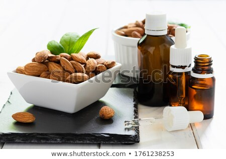 Stock photo: almond essential oil and almond in bowl