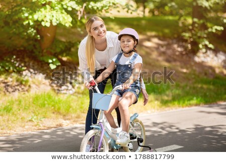 happy lady outdoors on bicycle looking camera stock photo © deandrobot