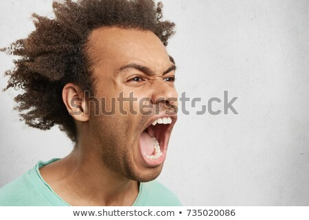 Close up portrait of a mad african man with stubble Stock photo © deandrobot