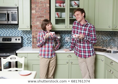 Young couple holding teacups in kitchen Stock photo © IS2