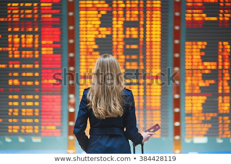 Woman with a passport looking on departure board Stock photo © Margolana