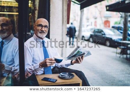 Senior man resting by car with newspaper Stock photo © IS2