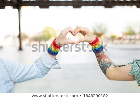 Stock photo: gay couple with rainbow wristbands and hand heart