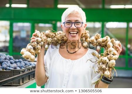 Senior woman buying lot of garlic on market Stock photo © boggy
