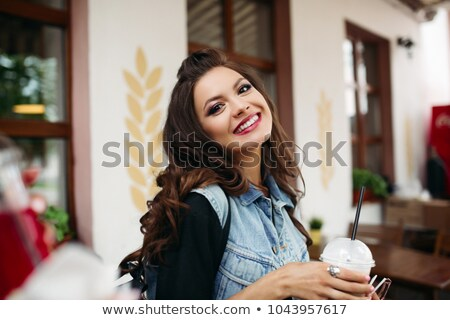 Pretty girl with brunette wavy hair in denim vest with drink in cafe. Stock photo © studiolucky
