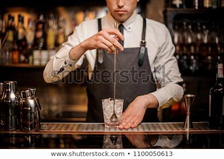 Bartender stirring cocktail Stock photo © Kzenon
