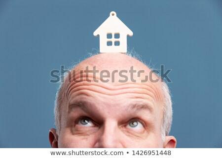Senior balding man looking up at a model house Stock photo © Giulio_Fornasar