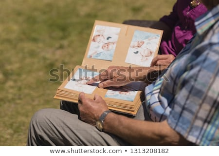 Mid section of senior woman looking photo album and showing one picture at her friend at home Stock photo © wavebreak_media