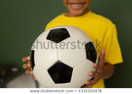 Mid section of happy mixed-race schoolboy with football looking at camera against greenboard in a cl Stock photo © wavebreak_media